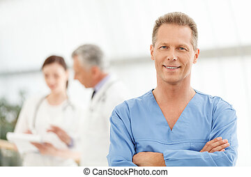 kun, den, bedst, medicinsk, treatment., portræt, i, en, raffineret, moden, mandlig doktor, ind, blå ensartede, beliggende, uden for, hans, kollegaer, og, smil