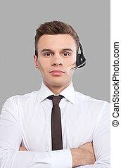 kund, hörlurar med mikrofon, medan, hans, representative., service, justera, grå, formalwear, ung, glad, stående, kamera, mot, bakgrund, leende herre