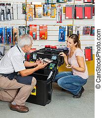 kunde, auswählen, werkzeuge, während, verkäufer, assistieren, sie, in, kaufmannsladen