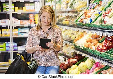 kunde, gebrauchend, digital tablette, während, shoppen, in, lebensmittelgeschäft