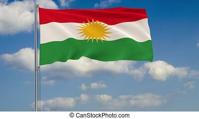 Kurdistan flag against background of clouds floating on the blue sky