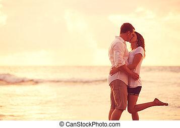 kussende , paar, strand, ondergaande zon , romantische