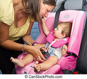 kvinde, fastening, hende, søn, på, en, baby sæde, en vogn
