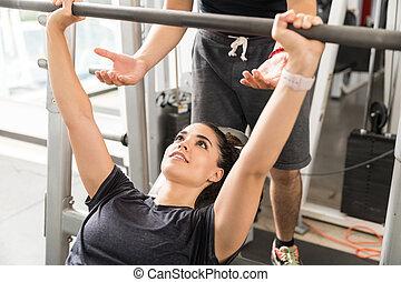 kvinde, gør, bænk press, mens, instruktør, bistå, hende, ind, gymnastiksal
