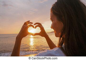 kvinde, indgåelse, hjerte, i, hænder, hos, solnedgang