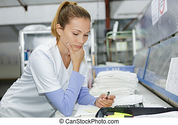 kvindelig, arbejder, ind, vask, hos, regnemaskine, gør, paperwork