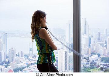 kvinna, ämbete telefonera, se, talande, utanför, fönster, avlyssnad