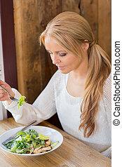 kvinna ätande, sallad, restaurang