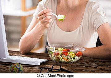 kvinna ätande, sallad