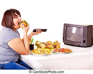 kvinna ätande, snabbmat, och, hålla ögonen på, tv.