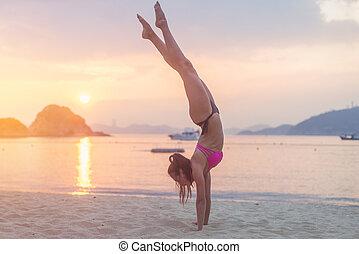 kvinna, öva, prålig, handstående, sunrise., ung, bikini, ...