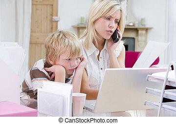 kvinna, användande, telefon, in, huvudkontor, med, laptop, medan, ung pojke