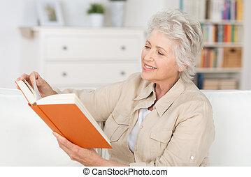 kvinna avkopplande, äldre, bok, hem, läsning