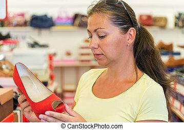kvinna, chooses, röd skor, in, a, lager, för, uppköp
