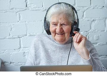 kvinna, gammal, headphones., laptop, främre del, bord, sitt