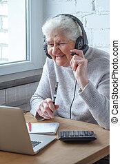 kvinna, gammal, laptop, hörlurar, notebook., främre del, bord, sitt, skriver