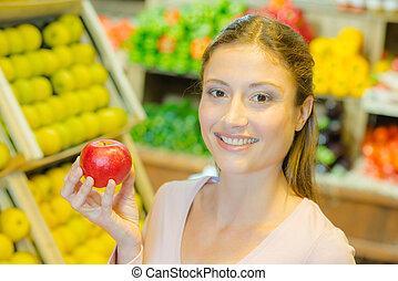 kvinna hålla rött äpple
