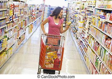 kvinna handling, in, supermarket, gång