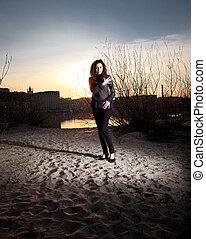 kvinna, in, fashionabel, kläder, stående, på, strand, hos, solnedgång