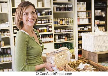 kvinna, in, marknaden, tittande vid, bread, le
