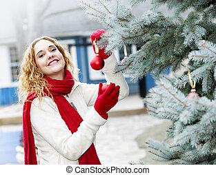 kvinna, inredande jul träd, utanför