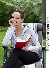 kvinna läsa en bok, in, trädgård