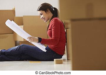 kvinna läsning, planer, av, nytt hus, under, flyttning