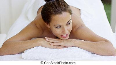 kvinna, leende, och, kopplar av, på, massage tabell