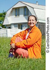 kvinna, lycklig, sittande, gräsmatta, front hemma