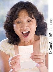kvinna, med, vinnande, lotteri lottsedel, spänd, och, le