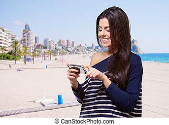 kvinna, mobil, nymodig, ung, mot, rörande, stående, strand