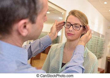 kvinna, optiker, erbjudande, ung, inramar, äldre hane, glasögon