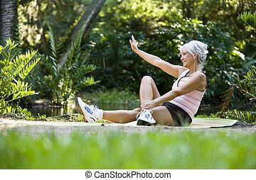 kvinna, på, matta, gör, sträckande, träningen, utomhus