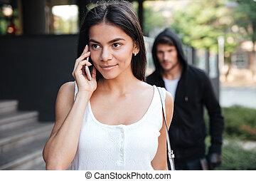 kvinna prata på rörlig, ringa, och, smyg, av, man, brottsling