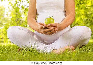kvinna räcka, grönt äpple, gravid