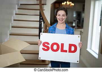 kvinna räcka, underteckna, såld, stående, vardagsrum