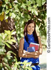 kvinna, sekvens, deltagare, träd, skola, parkera, ung, textbooks, högskola, böjelse, stående, leende glada