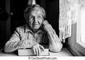 kvinna sitta, äldre, hand, bok, fönster., bord