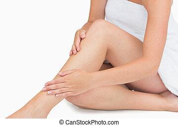 kvinna sitta, rörande, henne, ben