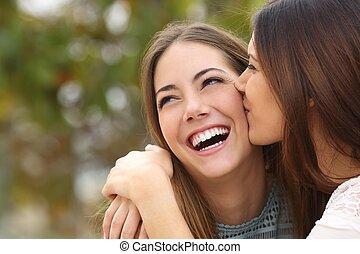 kvinna, skratta, med, göra perfekt tänder, medan, a, vän, är, kyssande, henne