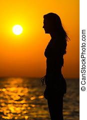 kvinna stå, hos, solnedgång