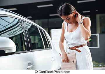 kvinna stå, och, se, stämm, av, bil, in, väska, utomhus