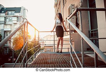 kvinna stå, på, balkong, med, metall, räckverk, hos, solnedgång