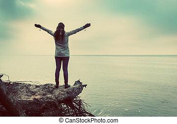 kvinna stå, på, brutet träd, på, vild, strand, med, beväpnar lyftt, betrakta sjögång