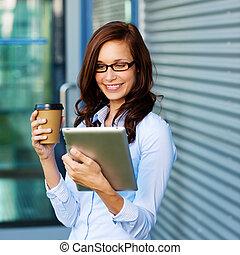 kvinna, supande kaffe, och, läsning, henne, tablet-pc