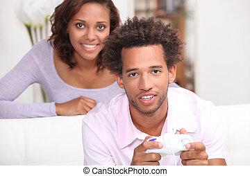 kvinna tittande, hos, henne, pojkvän, spelande video vilt