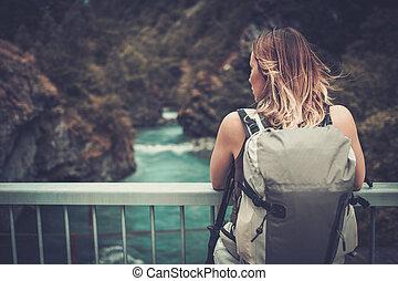 kvinna, vandrare, med, ryggsäck, stående, på, den, bro, över, a, vild, fjäll, river.
