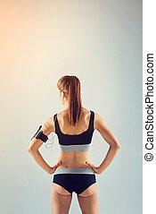 kvinnlig, atlet, vridet, baksida, musik lyssna, sportkläder