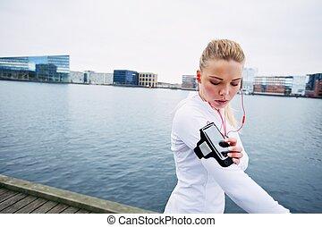 kvinnlig, joggare, övervaka, henne, framsteg, på, smartphone