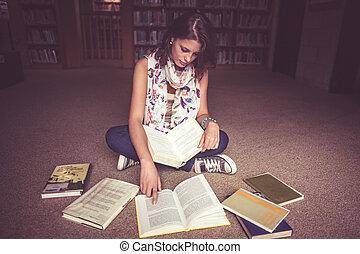 kvinnligt studerande, läsning en boka, in, bibliotek